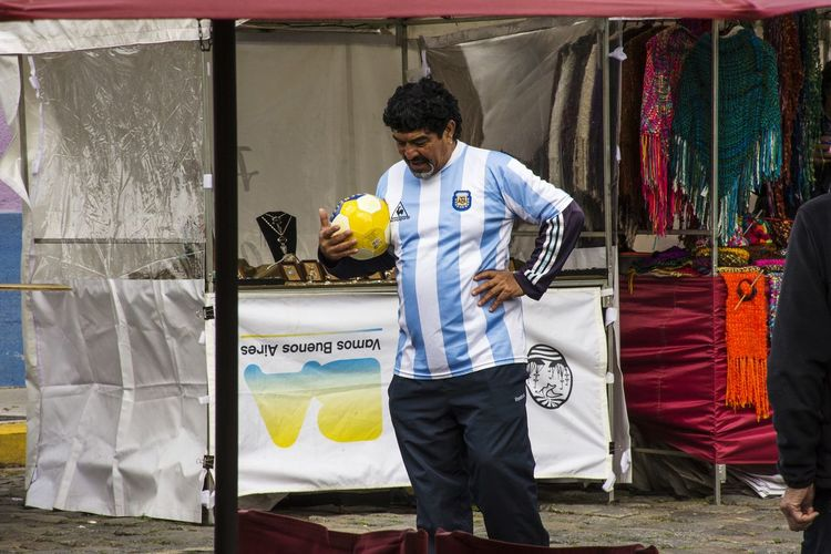 """El Diego"". Caminito, barrio La Boca. Bs As, Argentina 2018 Diego Armando Maradona Costume Imitator Men Business Standing Full Length Front View Portrait Casual Clothing Artist"