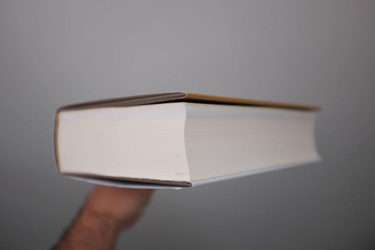Cropped image of person balancing book on finger against white wall
