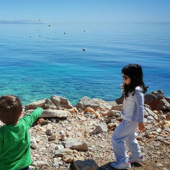 Blue Wave Showcase April Kids Enjoying Life Having Fun Seaside Capture The Moment Kidsphotography Capturing Freedom Sea View Capturing Movement My Kids Family Time Sunny Day Beautiful Day Seascape Shades Of Blue The KIOMI Collection Sea Water Sea Childsplay Throwing Rocks - Aegean Sea Greek Islands Chios Greece