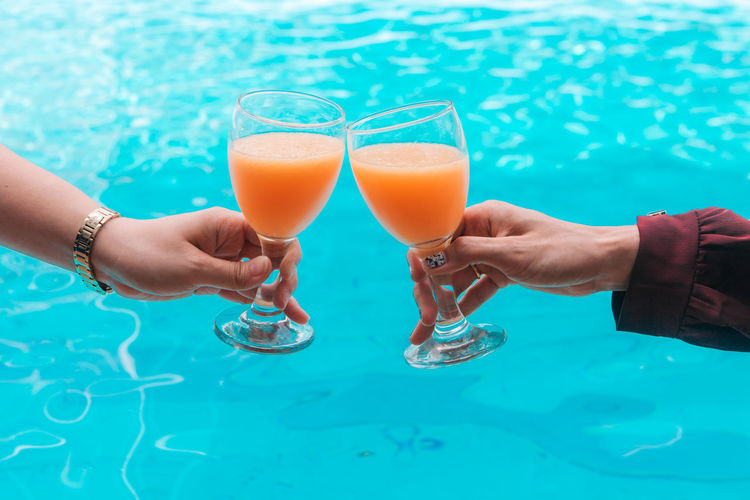 Adult Cocktail Couple - Relationship Drink Drinking Glass Food Food And Drink Freshness Glass Hand Holding Household Equipment Human Body Part Human Hand Leisure Activity Lifestyles People Positive Emotion Real People Refreshment Swimming Pool Two People Women