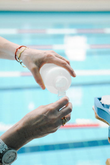 Cropped image of woman holding chemical against swimming pool