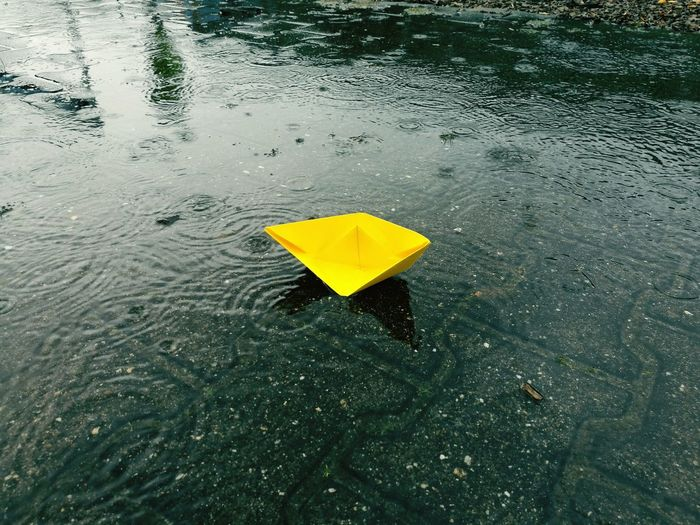 High angle view of yellow paper boat on puddle during rainy season