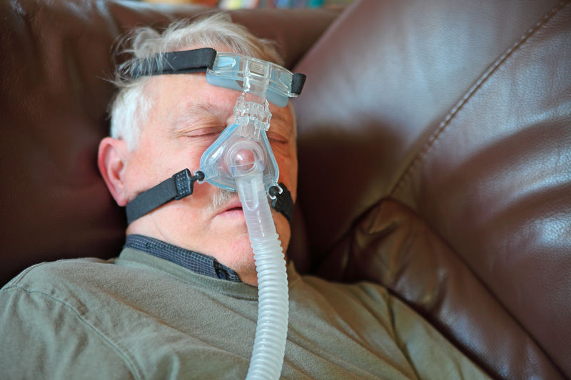 Senior man using sleep apnea attachment Senior Adult Close-up Indoors  Healthcare And Medicine Sofa Man CPAP Machine Sleep Apnea Medical Equipment Sleeping Napping Continuous Positive Airway Pressure Lying Down Natural Light Indoors  Casual Clothing Tubing Breathing Treatment Patient Older Person Straps Plastic