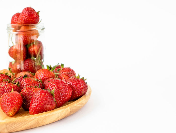 Close-up of strawberries in jar against white background