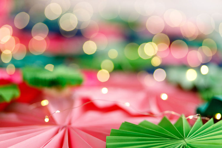 Colourful background with bokeh fairy lights Christmas Close-up Celebration Decoration Holiday Pattern Focus On Foreground Illuminated No People Shape Green Color Christmas Lights Leaf Christmas Decoration Paper Design Plant Part Plant Multi Colored Lens Flare Christmas Ornament Leaves