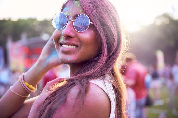 Portrait of beautiful woman wearing sunglasses at carnival