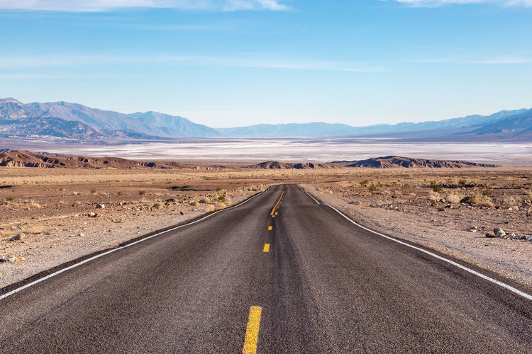 Looking down a road leading into death valley in california, with salt flats and a vast landscape