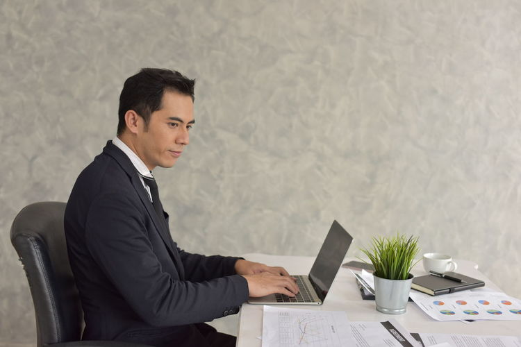 Business Person Businessman Business Young Men Office Young Adult Occupation Table Sitting One Person Men Technology Corporate Business Well-dressed Desk Indoors  Businesswear Working Waist Up Chair Wireless Technology