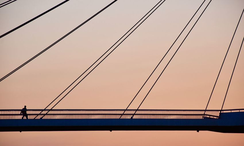 Man walking on a bridge during sunset 3XSPUnity Architecture Bridge Bridge - Man Made Structure Built Structure Cable Clear Sky Connection Creativity Day Exceptional Photographs Light And Shadow Minimalism Nature No People Outdoors Popular Photos Silhouette Simplicity Sky Sunset Suspension Bridge Symmetrical Symmetry Water Fresh On Market 2017 Colour Your Horizn Colour Your Horizn