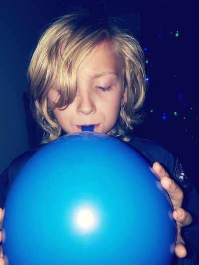 Close-up of boy blowing balloon at home