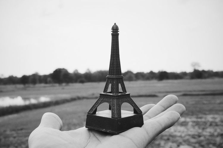 Cropped hand holding replica eiffel tower on landscape