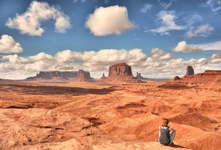Woman sitting on rock formations in desert against sky