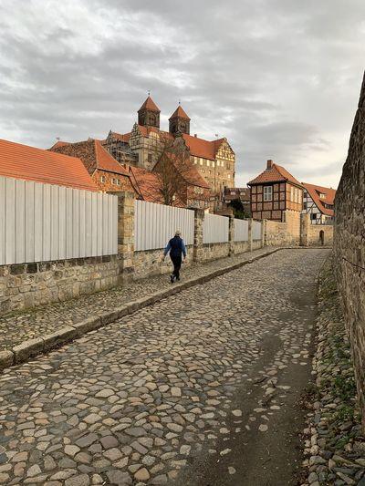 Man walking on footpath by building against sky