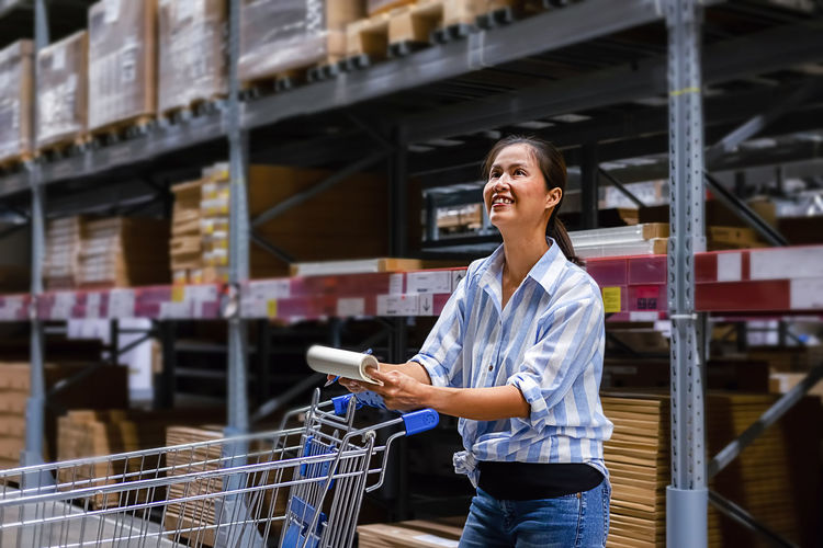 Smiling entrepreneur writing while standing in warehouse