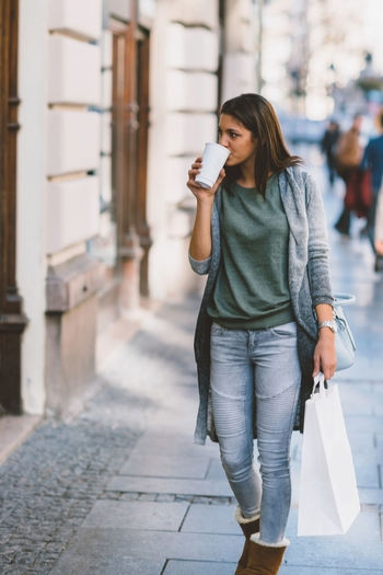 Full length of young woman having coffee while walking on sidewalk in city