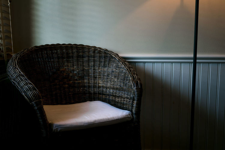 Close-up of empty chair against wall at home