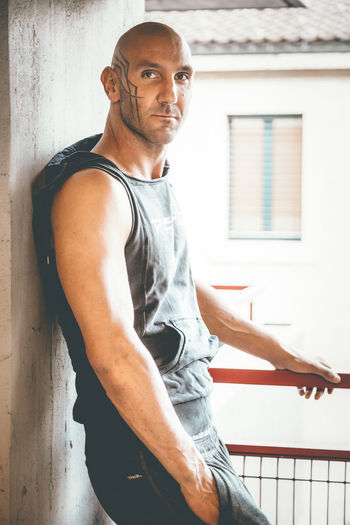 Muscular man leaning on wall in parking lot