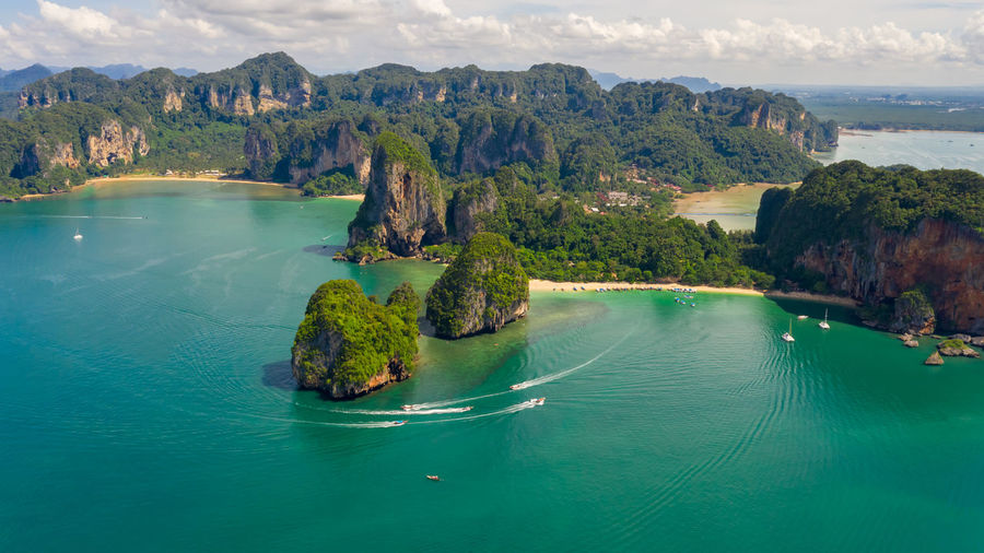 Aerial view seascape phra nang cave beach with traditional long tail boat sailing on the sea