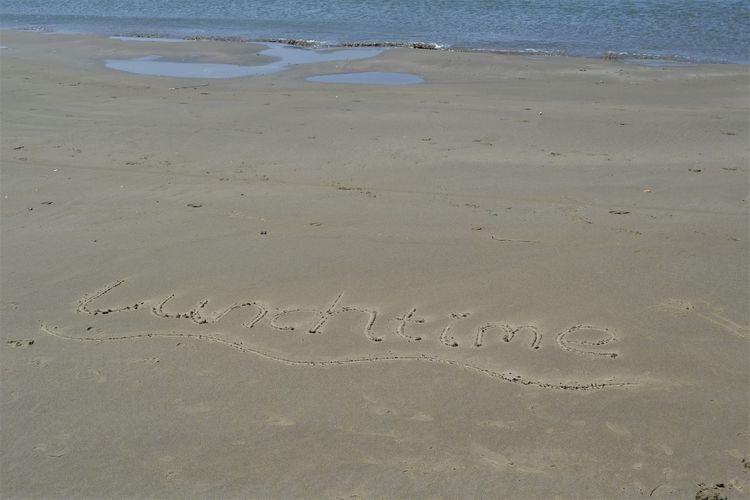 Lunchtime written in sand by the seashore and a hand drawing of a stick man. Hand Drawing Lunchtime Stick Man Beach Beach Art Beauty In Nature Communication Day Emotion High Angle View Land Love Message Nature No People Outdoors Positive Emotion Sand Sea Text Tranquility Water Western Script Writing