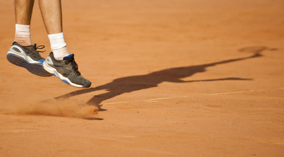 Low Section Of Tennis Player Jumping While Playing On Ground