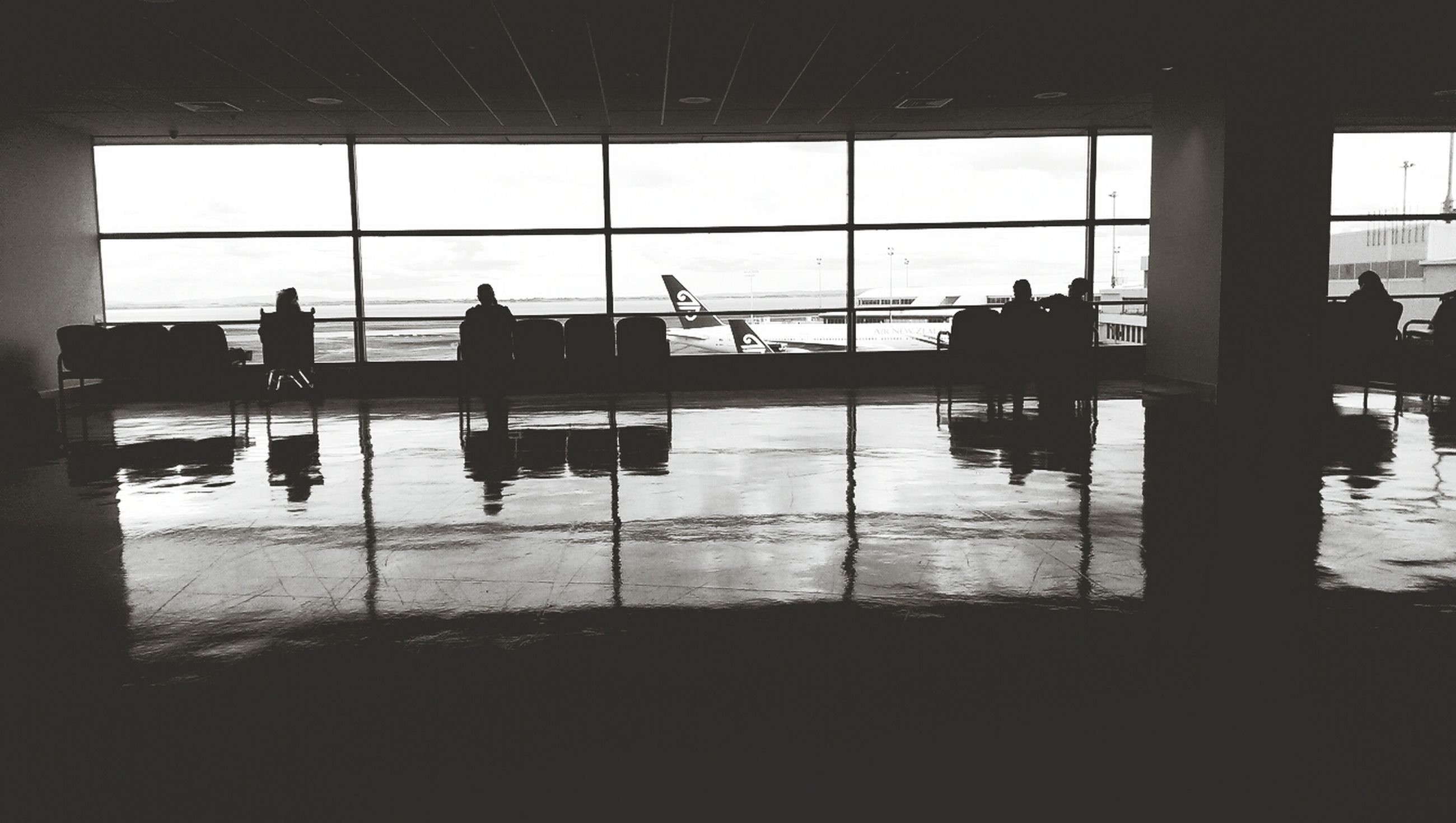 indoors, window, silhouette, glass - material, men, transparent, person, lifestyles, airport, medium group of people, leisure activity, built structure, sitting, unrecognizable person, travel, reflection, chair