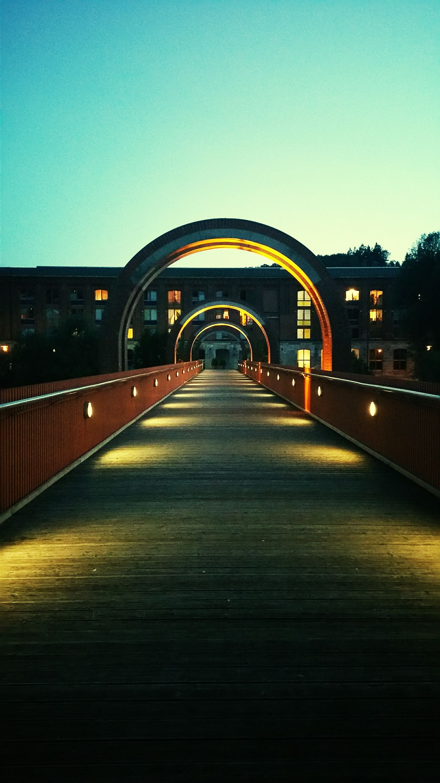 clear sky, illuminated, the way forward, built structure, night, architecture, copy space, diminishing perspective, arch, connection, bridge - man made structure, transportation, vanishing point, empty, road, lighting equipment, street light, long, bridge, surface level