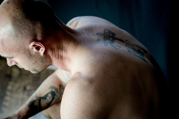 High Angle View Of Shirtless Shaved Head Man With Tattoo Sitting Indoors