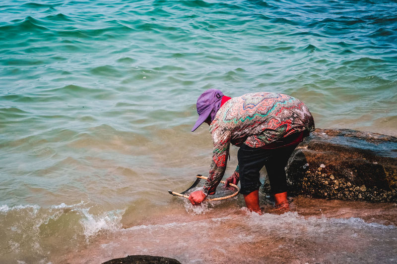 Side view of woman fishing in sea