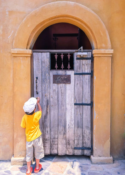 Rear View Of Boy Knocking Wooden Door