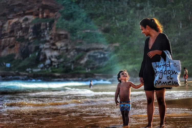 Mother With Son Standing At Beach Against Mountain