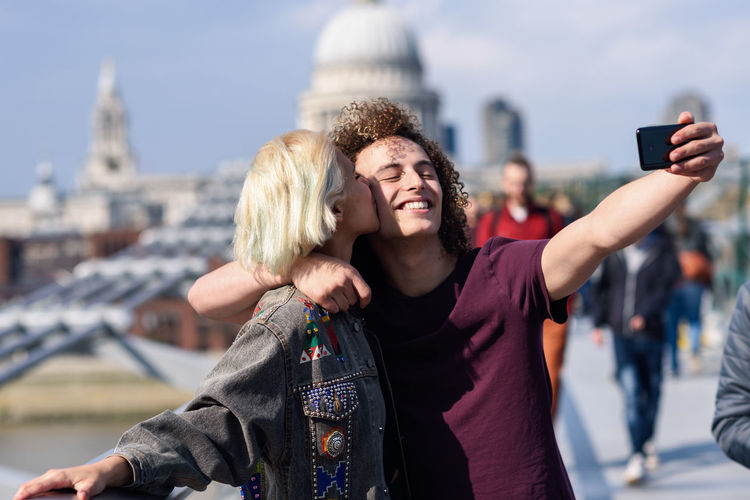 Smiling man with girlfriend taking selfie with mobile phone on footbridge in city