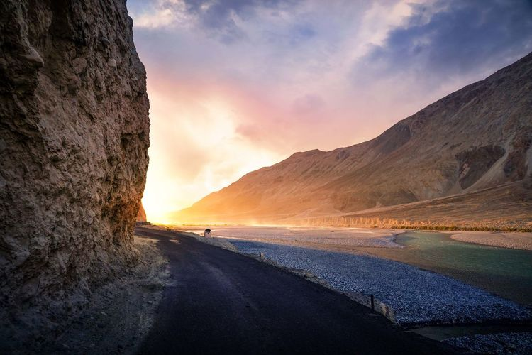 Road by mountains against sky during sunset