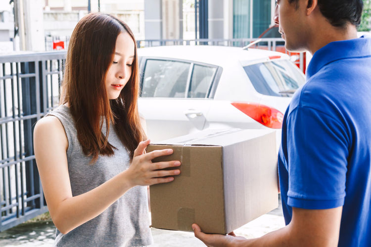 Woman accepting a delivery boxes from delivery man Adult Architecture Box Box - Container Cardboard Casual Clothing Couple - Relationship Day Land Vehicle Lifestyles Men Mode Of Transportation Motor Vehicle People Real People Standing Transportation Two People Waist Up Women Young Adult Young Women