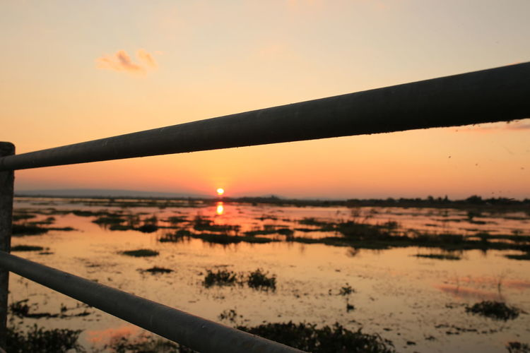 Sunset on lake Sunset Sky Orange Color Nature Beauty In Nature Scenics - Nature Water No People Sun Outdoors Silhouette Cloud - Sky Tranquility Tranquil Scene Security Protection Railing Safety Non-urban Scene Landscape Nong Han Lake Nuture Viewpoint Sakon Nakhon