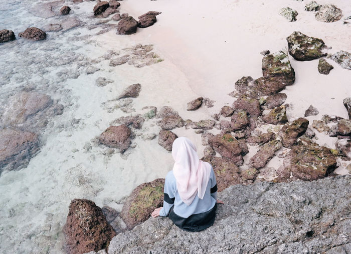 Rear view of woman sitting on rock by sea