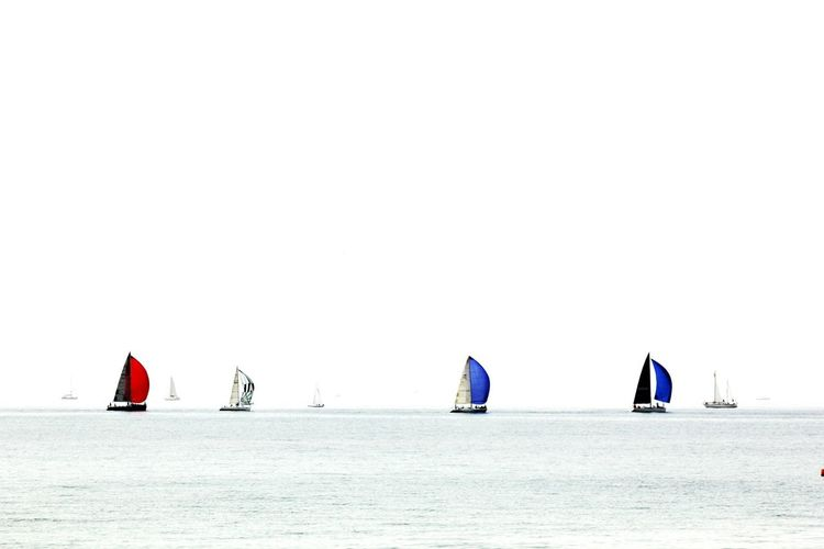 Boats Sailing At Sea Against Clear Sky