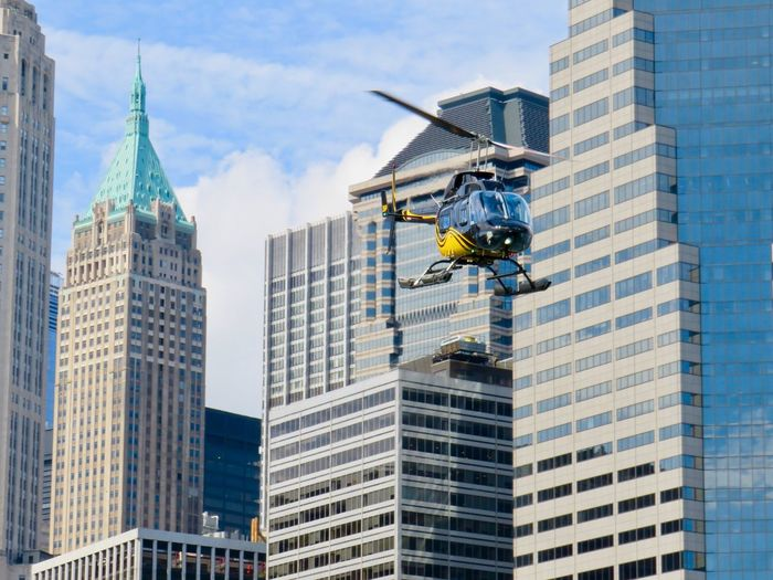 Low angle view of helicopter flying against buildings in city