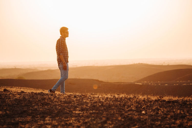One Person Sky Sunset Full Length Nature Sunlight Casual Clothing Mountain Back Lit Scenics - Nature Leisure Activity Standing Adult Copy Space Land Landscape Beauty In Nature Side View Lens Flare Outdoors