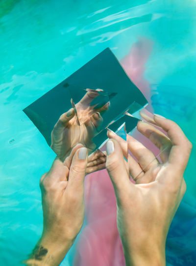 Cropped hands of woman holding mirror and prism in swimming pool