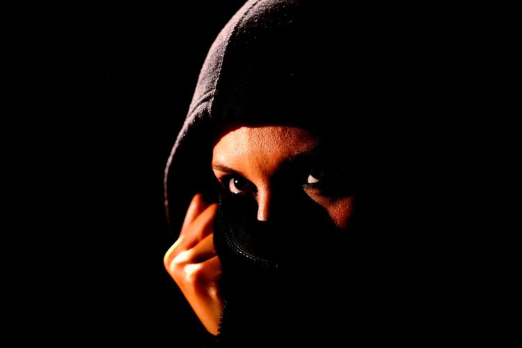 Close-up of woman covering face against black background