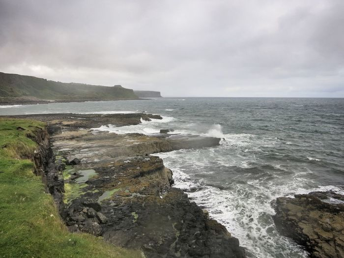 View of rocky coastline against cloudy sky