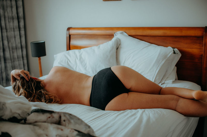 Rear view of shirtless woman lying on bed at home