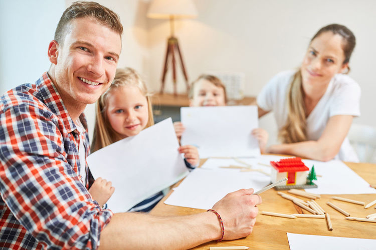 Portrait of cheerful family doing drawing at home