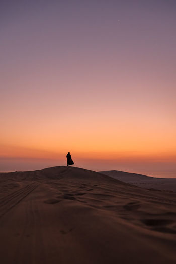 Silhouette woman standing on sand dune against sky during sunset