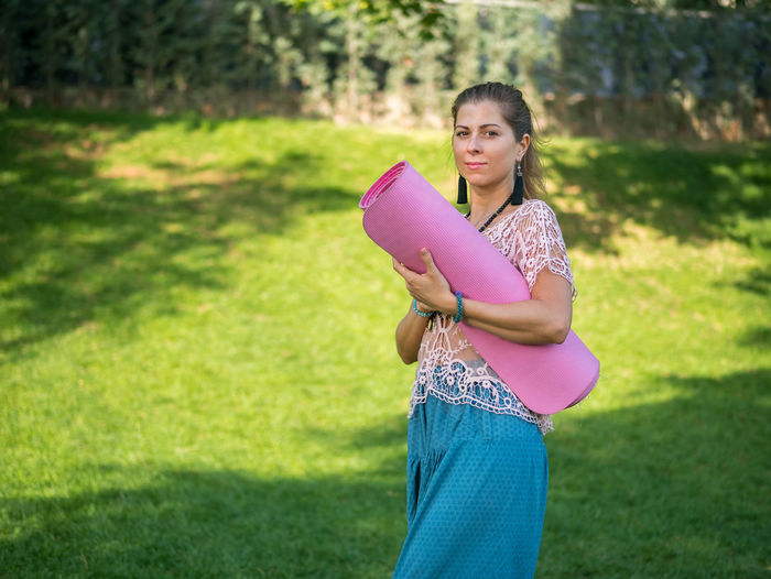 Young Woman Holding Exercise Mat While Walking On Grassy Field