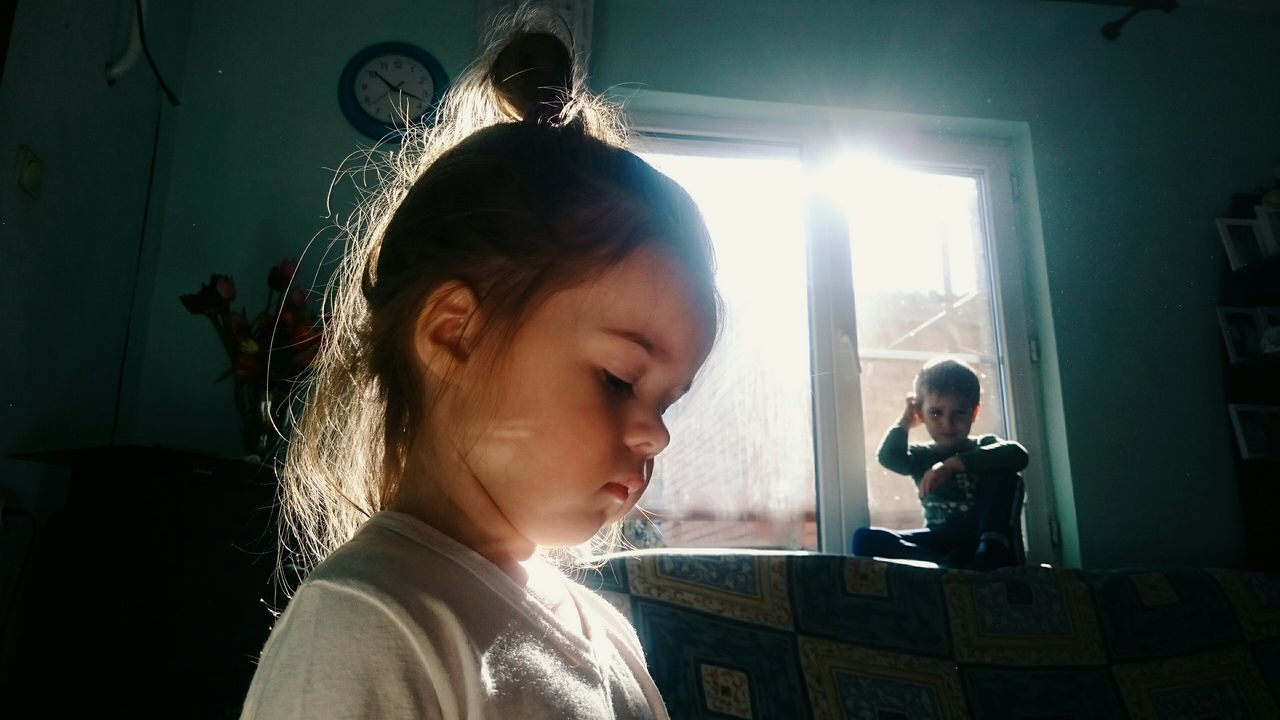 Close-up of girl with boy sitting by window at home