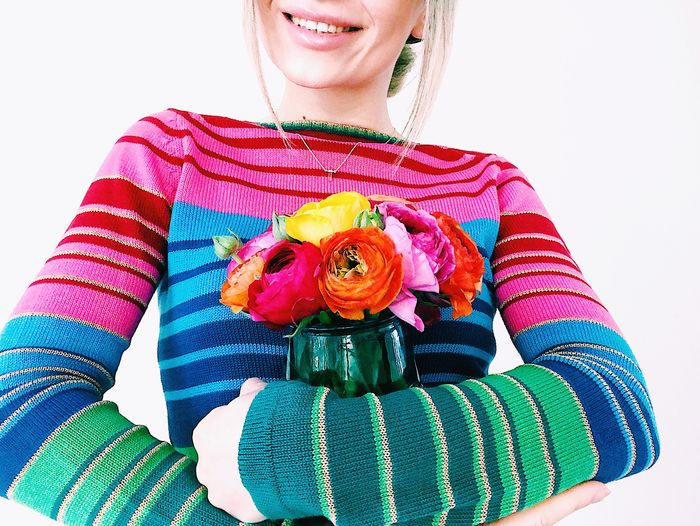 Midsection of woman holding bouquet against white background