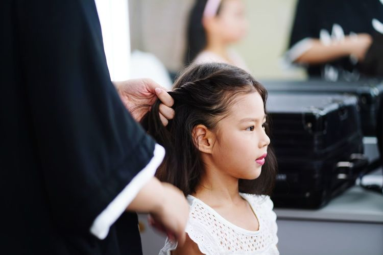 Midsection of hairdresser holding girl hair in beauty spa