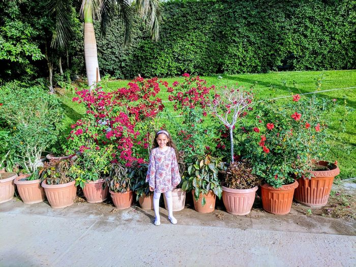 Girl Standing Against Potted Plants