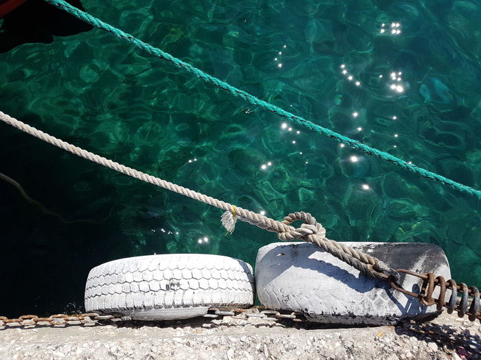 High angle view of rope tied to fishing net at harbor